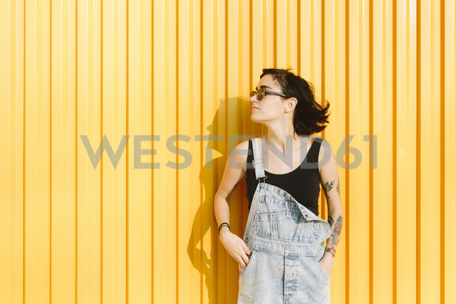 Young woman standing against a yellow wall - GIOF000656 - Giorgio Fochesato/Westend61