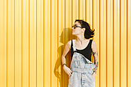 Young woman standing against a yellow wall - GIOF000656