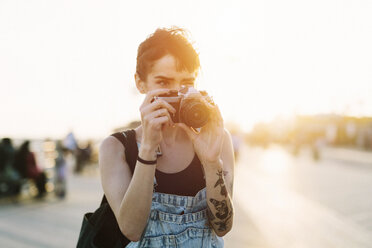 USA, New York, Coney Island, young woman  taking photos at sunset - GIOF000665