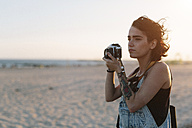 USA, New York, Coney Island, young woman  taking photos on the beach at sunset - GIOF000671
