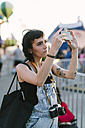 USA, New York, Coney Island, young woman taking a selfie at the amusement park - GIOF000674