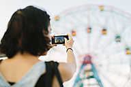 USA, New York, Coney Island, young woman taking a cell phone picture at the amusement park - GIOF000677