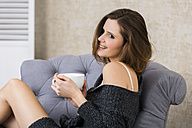 Smiling brunette woman in armchair holding cup of coffee - SHKF000461