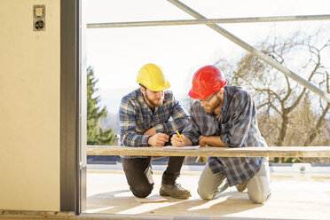 Two craftsmen discussing and taking notes in construction site - LAF001592