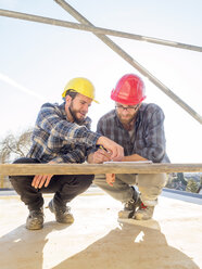 Two craftsmen discussing and taking notes in construction site - LAF001595