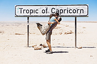 Namibia, Namib desert, Swakopmund, traveler couple kissing next to the sign of the Tropic of Capricorn - GEMF000631