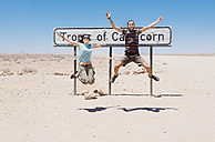 Namibia, Namib desert, Swakopmund, traveler couple jumping next to the sign of the Tropic of Capricorn - GEMF000643