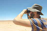 Namibia, Namib desert, man with hat using binoculars to look away - GEMF000646