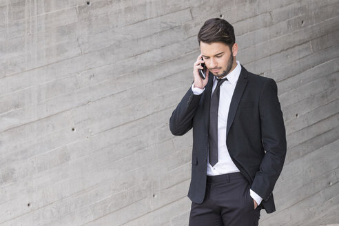 Businessman wearing black suit telephoning with smartphone - SIPF000072