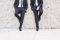 Two businessmen wearing black suits leaning side by side against wall - SIPF000075