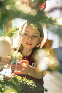 Portrait of girl decorating Christmas tree - SARF002467