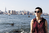 USA, New York City, portrait of smiling young woman wearing sunglasses - GIOF000682