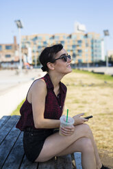 USA, New York City, Brooklyn, young woman sitting on a bench holding smartphone and plastic cup - GIOF000685