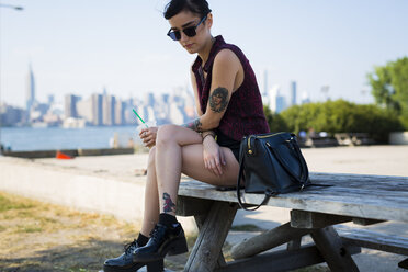 USA, New York City, Brooklyn, tattooed young woman sitting on a bench - GIOF000688