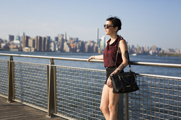 USA, New York City, Williamsburg, tattooed young woman leaning on a railing - GIOF000697