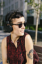 Portrait of tattooed young woman with headphones and sunglasses - GIOF000706