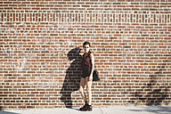 Portrait of young woman leaning against brick wall - GIOF000712