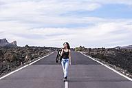 Spain, Tenerife, woman walking on an empty road - SIPF000112