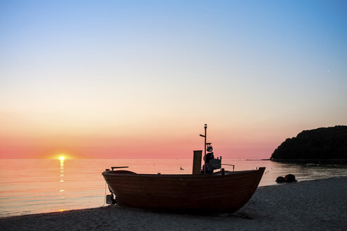 Germany, Ruegen, Binz, Beach with fishing boat at sunset - PUF000460