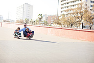 Spain, Catalonia, Barcelona, Uncle and kids doing skate board - VABF000065