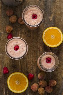 Buttermilk smoothie, orange, litchi and raspberries on wood - ODF001363