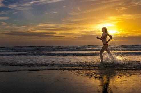 Woman wearing bikini jogging at the sea - DIGF000012