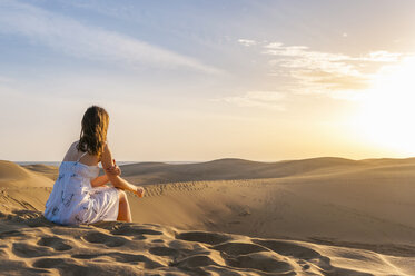 Woman sitting on dune, contemplating - DIGF000015