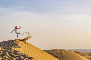Woman on dune kicking sand - DIGF000018