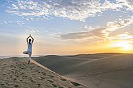 Woman practising yoga on sand dunes - DIGF000024