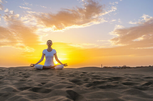 Woman practising yoga on sand dunes - DIGF000030