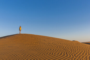 Woman walking over sand dunes - DIGF000033
