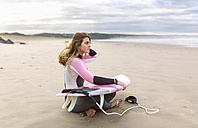 Young surfer woman sitting on the beach - MGOF001286
