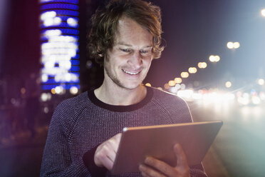 Germany, Munich, portrait of smiling man using digital tablet at night - RBF004071