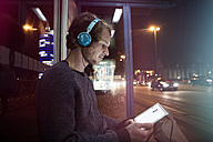 Germany, Munich, man with headphones sitting at bus stop using digital tablet at night - RBF004074