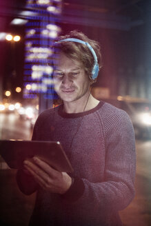 Germany, Munich, man with headphones using digital tablet at night - RBF004077