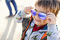 Portrait of smiling little boy putting on coloured sunglasses - VABF000073