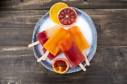 Plate of different homemade orange ice lollies and orange slices - SARF002479