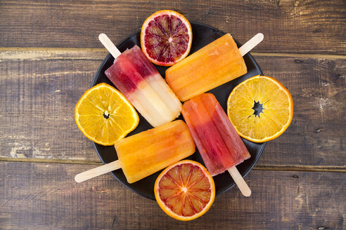 Plate of four different homemade orange ice lollies and four orange slices - SARF002482