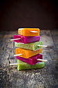 Stack of fruit smoothie ice lollies on dark wood - LVF004457