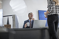 Businessman at desk with cup of coffee looking at colleague - ZEF007963