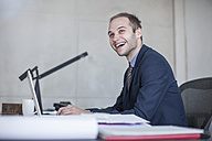 Laughing businessman at desk looking up - ZEF007966