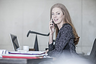 Smiling woman at desk on the phone - ZEF007969