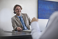 Smiling businessman at desk with laptop looking at man - ZEF007987