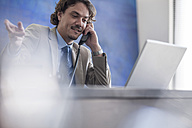 Businessman at desk with laptop on the phone - ZEF007990