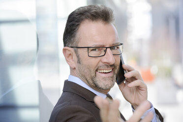 Portrait of smiling businessman telephoning with smartphone while pointing on viewer - GUFF000248