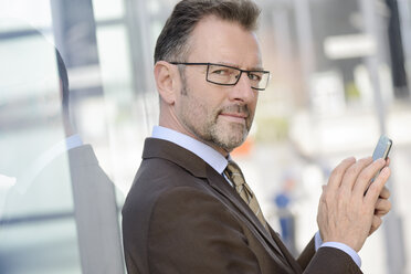 Portrait of businessman with spectacles and smartphone - GUFF000251