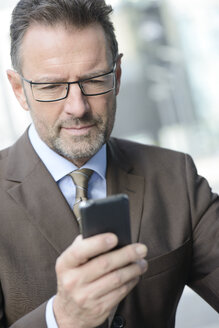 Portrait of businessman with spectacles looking at his smartphone - GUFF000254