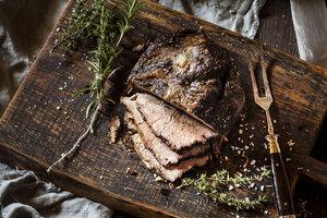 Sliced roast beef, rosemary, thyme and sea salt on chopping board - SBDF002649