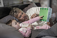 Man reading book with baby girl - ZEF008091