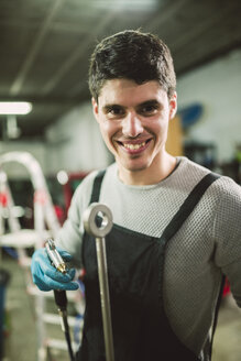 Young mechanic working in repair garage - RAEF000793